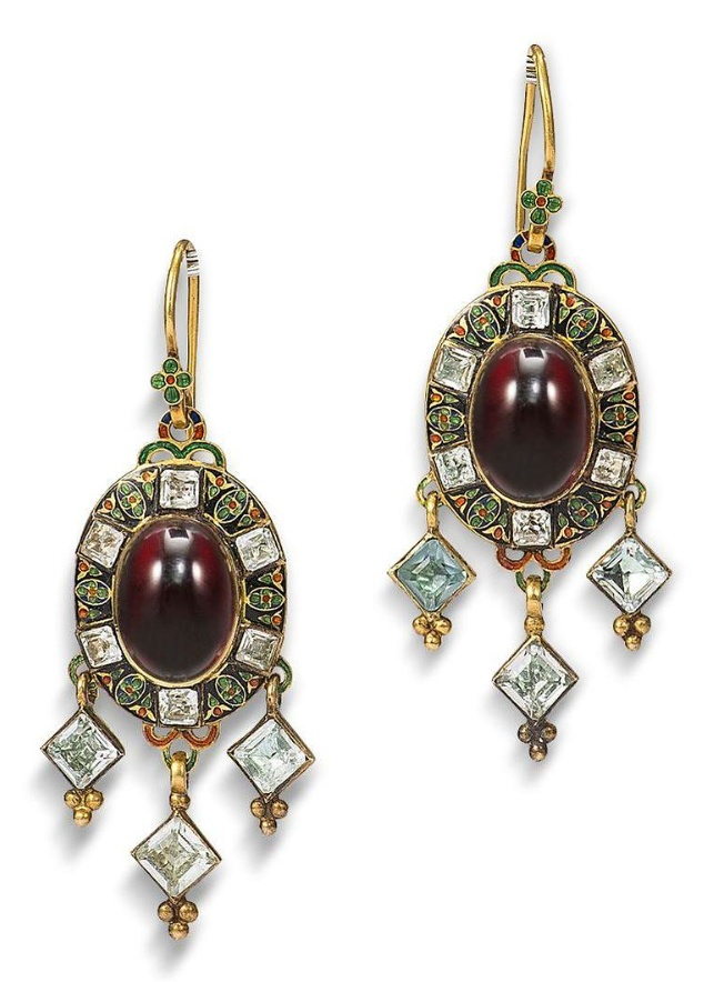 A Holbeinesque brooch and earring suite, circa 1865  The brooch set to the centre with a cabochon garnet, within a champlevé enamel border in shades of blue, green and red and six cushion-shaped chrysoberyls, terminating in a lozenge-shaped chrysoberyl drop, mounted in gold, the reverse with glazed compartment and engraved foliate motifs, converted from a pendant, accompanied by a matching pair of earrings [Earrings only]