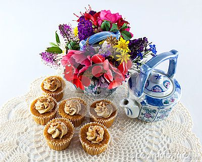 Toffee cupcakes with cream frosting on lace doily with two painted teapots and garden flowers.