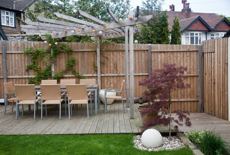 An Acer palmatum with a small globe water feature fill the corner of the grass and provide height from the decking