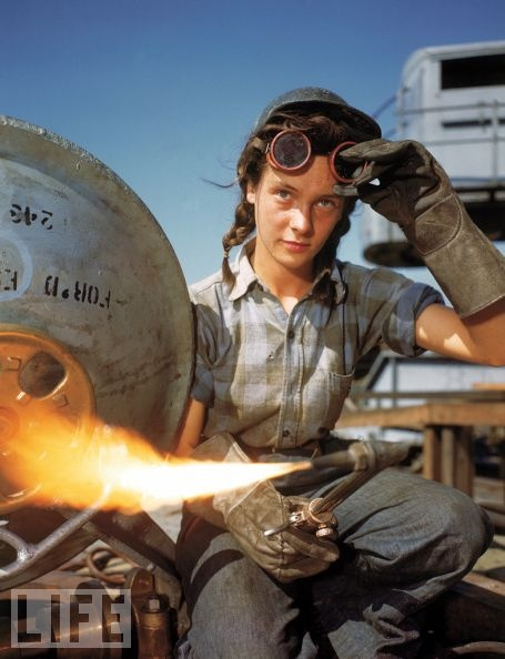 A welder at a boat-and-sub-building yard adjusts her goggles before resuming work, October, 1943. By 1945, women comprised well over a third of the civilian labor force (in 1940, it was closer to a quarter) and millions of those jobs were filled in factories: building bombers, manufacturing munitions, welding, drilling, and riveting for the war effort.