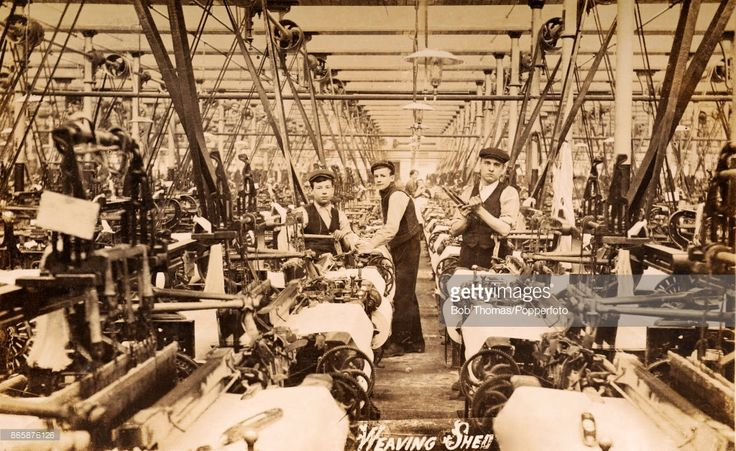 Labourers at work in a weaving shed in a textile manufacturing factory in Bristol, circa 1920.