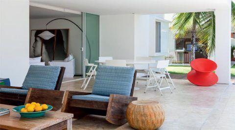 Portas amplas tornam a varanda um prolongamento da sala. Duas poltronas de balanço Astúrias, de Carlos Motta (Básica Home), criam um espaço para a conversa.