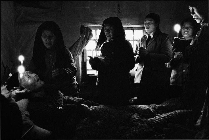 """CHINA. Shaanxi Province. 1994. The 83-year-old Li Zhen is dying, as members of her family and other believers pray around her. """"Pray more, for for my sake"""" were her last words."""