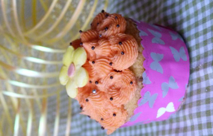 cupcake de naranja perlitas de chocolate y flor en fondant.