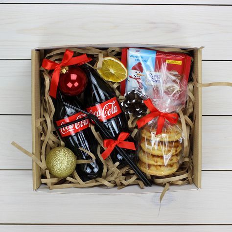 В комплект входит: Кока-кола, ёлочные игрушки, шоколад Риттер Спорт, печенье ...