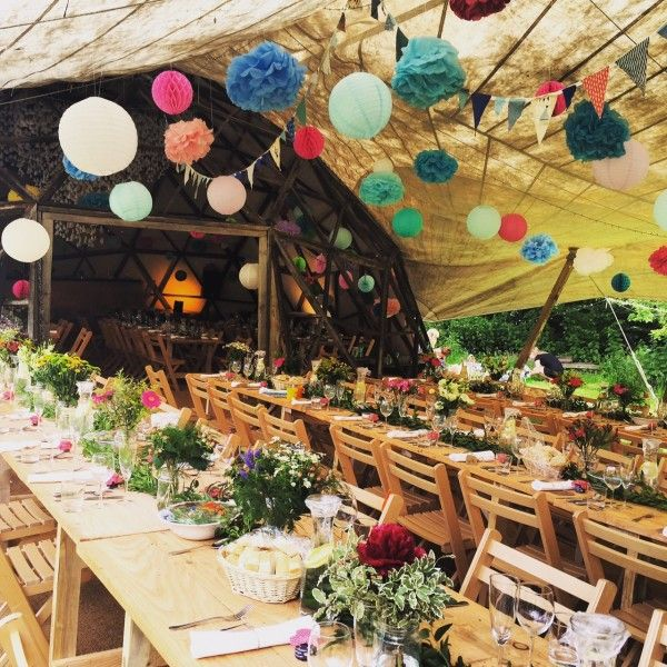 Festival Wedding Decor - wooden trestle tables, bright flowers, marquee, canopy, lanterns