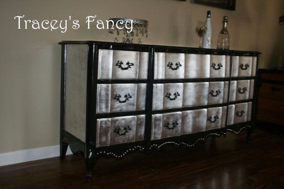 I have used a high gloss black paint on the body of the dresser. I silver leafed the drawer fronts and sides. The bottom edging is lined neatly with silver tacks. $950