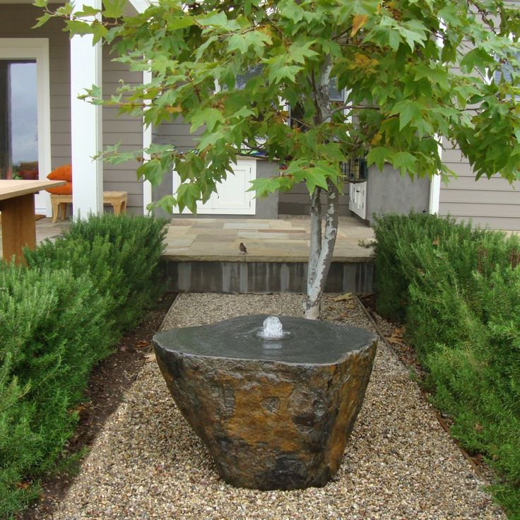 cut boulder used as water feature in a small space pebbles and the japanese maple