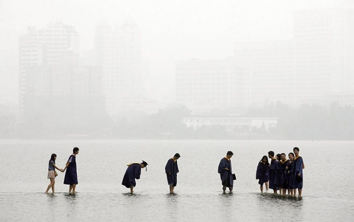 "unearthedviews: "" Wuhan, China: Students in graduation robes stand on a stone bridge submerged by floodwaters on Donghu Lake Darley Wong /Reuters """