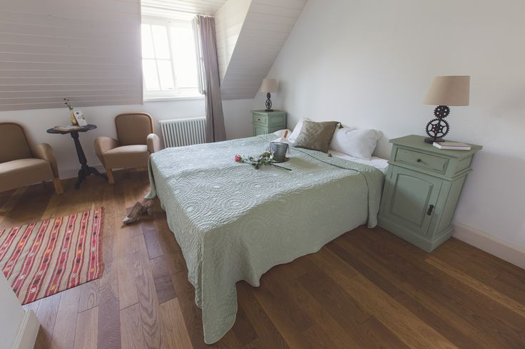 Romantic style bedroom with a comfy double bed, champagne and roses