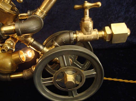 Up for Sale is a Steampunk Lamp featuring an Industrial Age Robot, riding a Steampunk Motorcycle/Tryke. This Desk or Table Lamp Features Steampunk and Industrial Age Styling using Vintage Parts and New Electrical Components. It Features Vintage Brass Valves, Gears, and Pipe