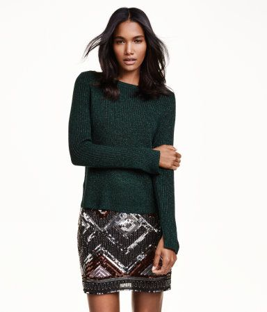 울을 함유한 골지 니트 스웨터. 뒷면이 메리야스 뜨기로 마감됨. 옆면 하단과 소맷단에 트임이 있으며, 뒷면이 좀 더 긴 스타일.