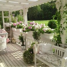 This shabby chic porch is lovely with the flower boxes, vines, and seating