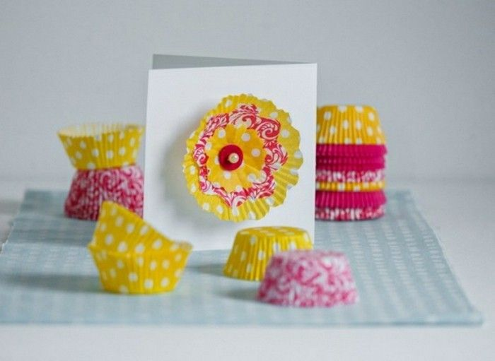 easy kids crafts, flower made from muffin moulds, pinned on a white card, many yellow and pink patterned muffin moulds, stacked together and loosely placed on table