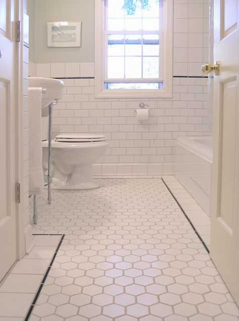 white hexagonal bathroom floor tile with white border separated with black stick detail and white subway tile on the walls with white cove base and mudcap