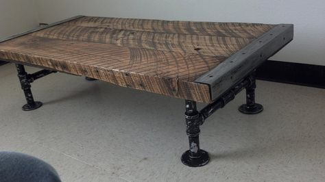 Industrial coffee table made of reclaimed wood and pipes.