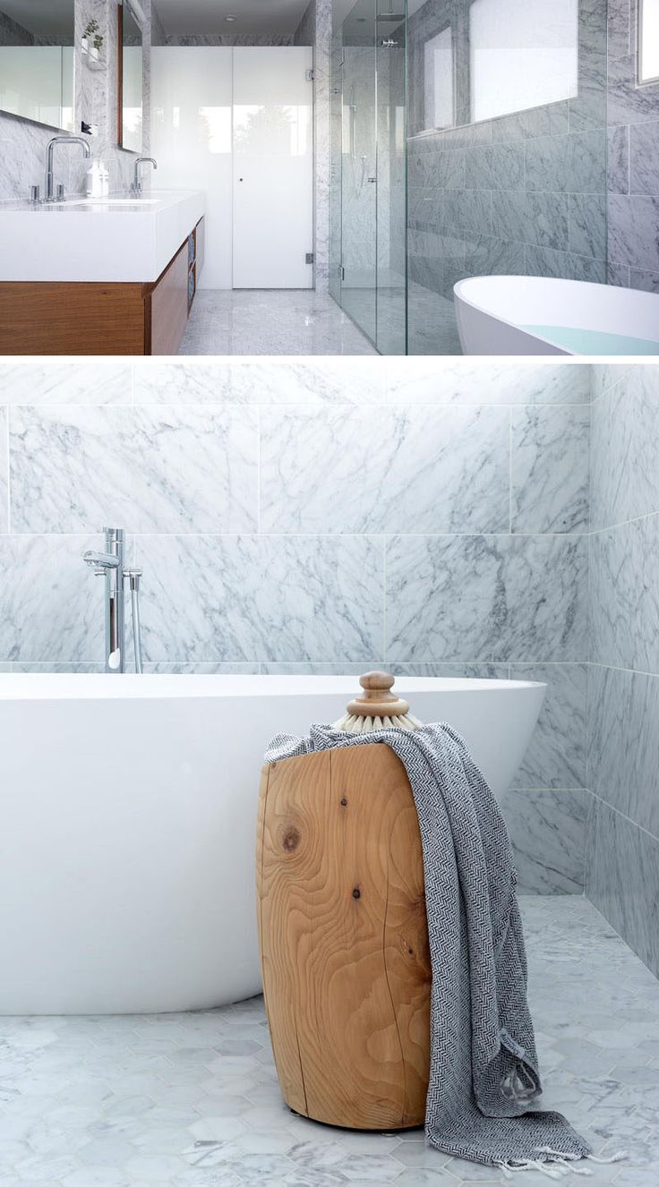 This modern bathroom has white Carrara marble for the floors and walls, a glass shower surround, a white quartz countertop and a walnut vanity.