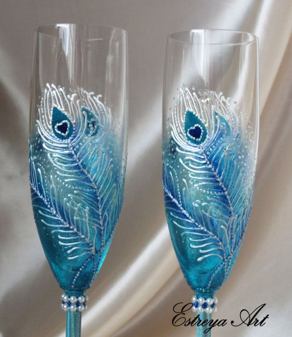 """Set of two hand painted toasting flutes """"Peacock feathers in blue"""" These elegant and colorful glasses with peacock feathers are in white, blue, turquoise and blue with a hint of glitter. The myth of peacock represents fidelity, as it dies of grief, or remains single, if it loses its mate. The Peacock brings harmony and reminds of joy to our mind. They are unique and perfect present for weddings, anniversaries, birthdays, special occasions or just for romantic /special dinners. All item..."""