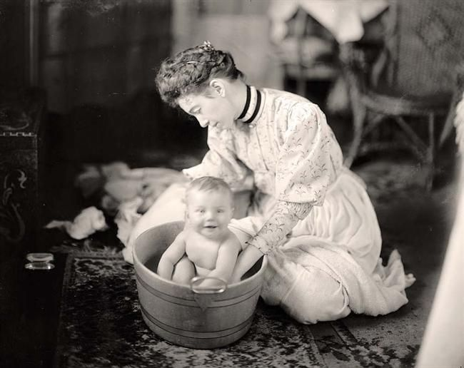 Woman Washing Baby. Early 1900s