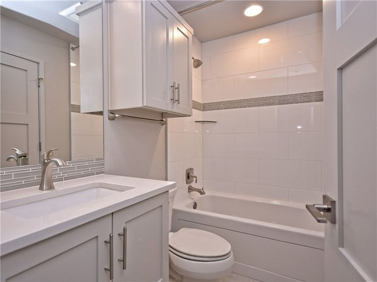 """Spa-esq guest bathroom! Custom tub wall tile with 4"""" accent band which is duplicated for the countertop backsplash under the mirror"""