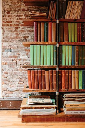 Salvaged wood, gas pipe, and scaffolding clamps make the shelves that hold Lauderdale's collection of vintage magazines, newspapers, and the...
