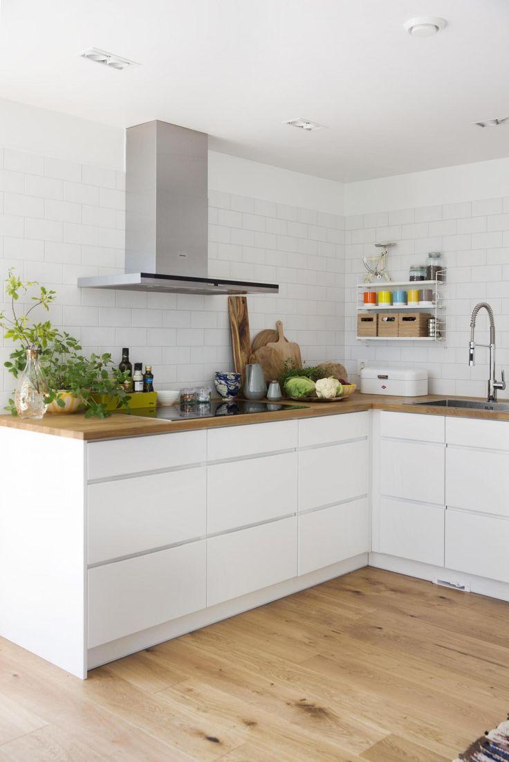 RENE LINJER: Kjøkkeninnredning Mano fra Kvik med benkeplate i eik, induksjonsplate og hette fra Siemens. Hvite fliser i størrelse 10 x 20 cm fra Vitra. Foto: Yvonne Wilhelmsen