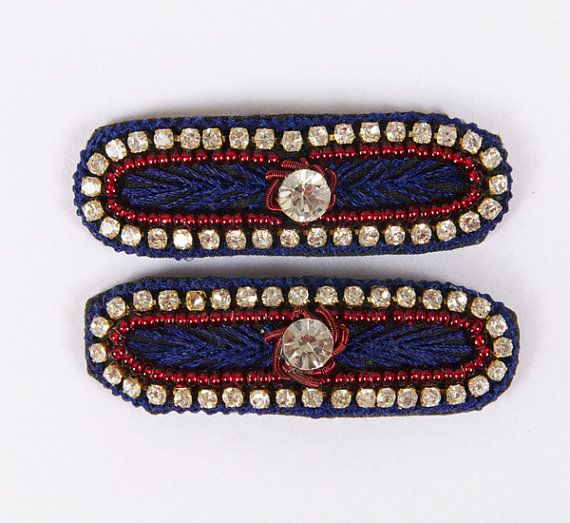 Navy blue thread edging with diamonds and red beading embroidery with one big diamante in the center. Snap clip, diamantes, hand embroidered. Navy, Red, Beading, Diamante, Round Crystal. Rectangle with rounded edges; Approx. 1 1/2 inches length by 1/2 inch width. Unique and beautiful on young girls and adults. £8.00 on Etsy... Please click on the Etsy link to purchase.