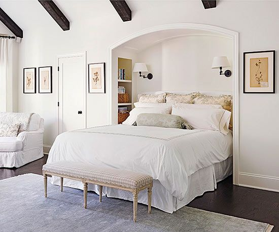 A clever niche cocoons the bed in the bedroom. Built-in shelves and sconces eliminate the need for bedside tables. Exposed beams emphasize high ceilings, and white walls and trim keep the room feeling spacious. Hints of gray