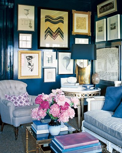 At a Chicago apartment decorated by Nate Berkus and Anne Coyle, the library's glossy walls, painted in Farrow & Ball's Off-Black, serve as a striking backdrop for an eclectically framed mix of artwork. The sofa's striped upholstery and an ikat pillow by Madeline Weinrib add graphic touches.
