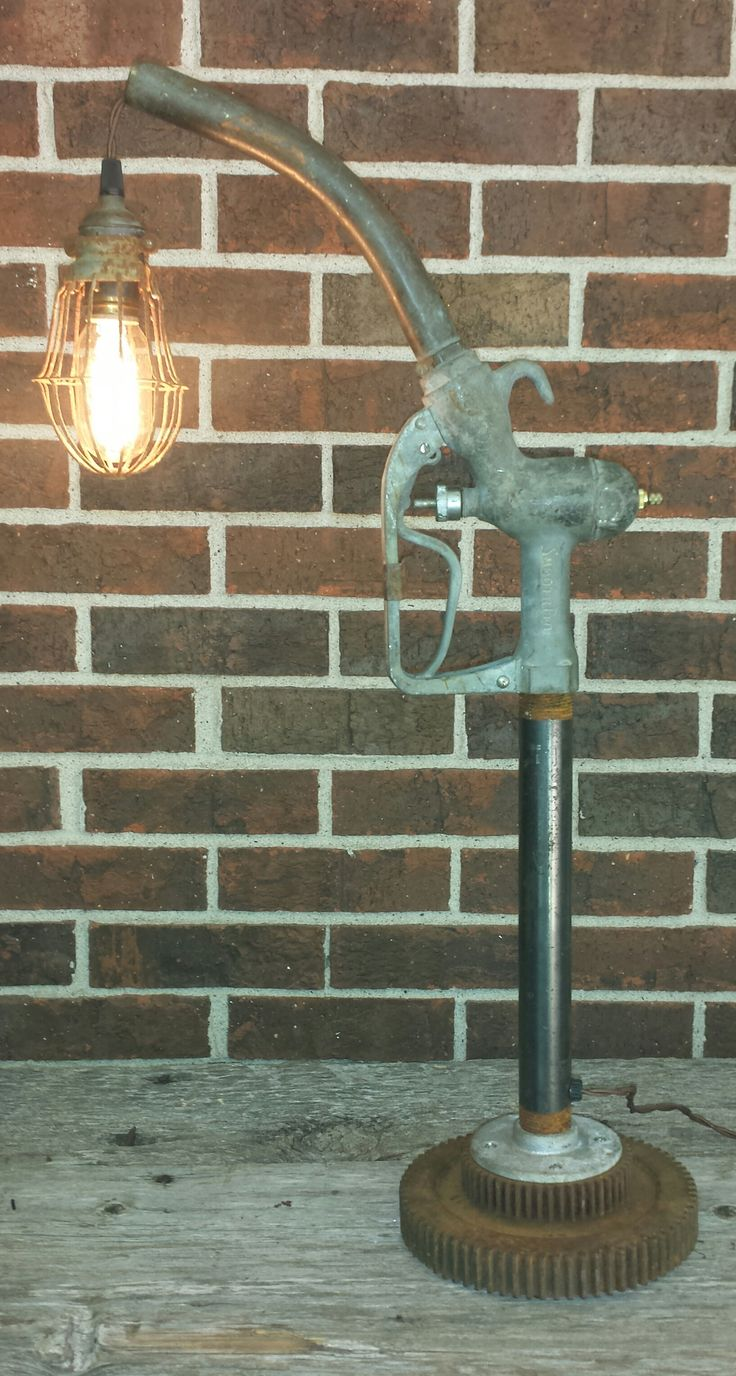 Custom table lamp using repurposed vintage trouble light, gas pump nozzle and cast iron gears. Available at #antiquearchaeologynashville #2lanessouth #davidphillipsdesigns #industriallamp #mikewolfeamericanpicker #customlamp