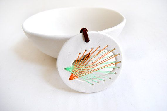 Ceramic String Art pendant made with white clay and transparent glaze. The threads are in a beautiful combination of green and orange colors, the