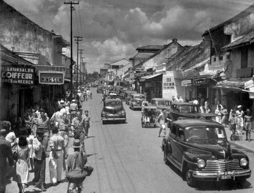Onder andere auto's en Nederlandse militairen in een winkelstraat in Bandoeng, Indonesië, circa 1947.