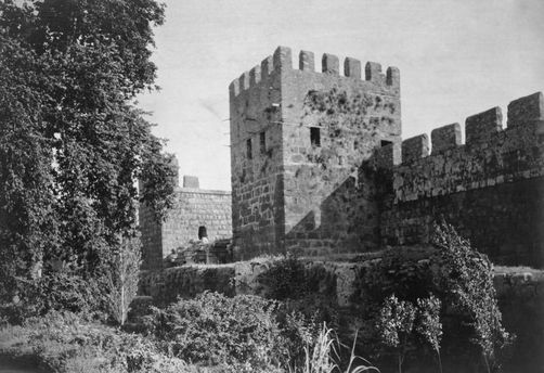 Vegetation climbs up medieval stone crenelated fortress walls. 1910s.  Location: Antalya, Turkey.  Photographer: ERNEST LLOYD HARRIS/National Geographic Creative