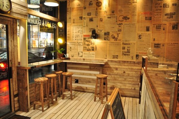 Piccolo Cafe, NYC. Welcoming rustic design - love the walls plastered with vintage newspaper, unfinished timber floorboards & bar seating.