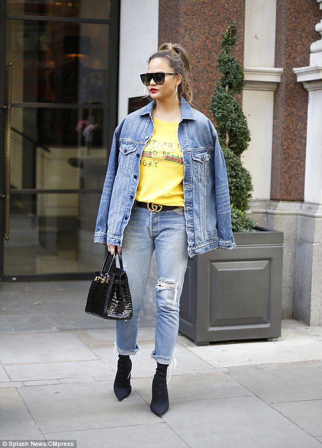 Chrissy Teigen wore Alexander Wang denim jacket, a bright yellow Gucci T-shirt, Re/Done jeans, Hermes bag, YSL sunglasses and Balenciaga boots.