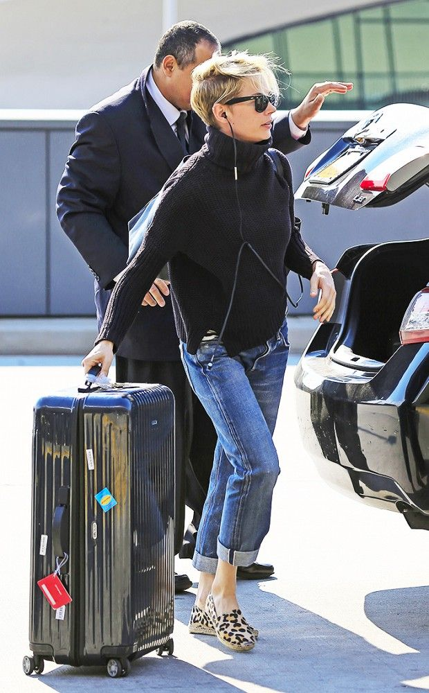 Michelle Williams wears a black turtleneck, cuffed jeans, and leopard espadrilles
