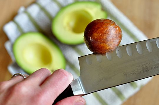 What is the best way to remove a pit from an avocado? / Slice the avocado in half lengthwise and then firmly strike the pit with the heel of a chef's knife. The knife lodges a few millimeters into the pit. To protect your fingers and give you a firmer grasp on the avocado, hold it with a folded kitchen towel. Also, definitely use a chef's knife for this, not a paring knife.