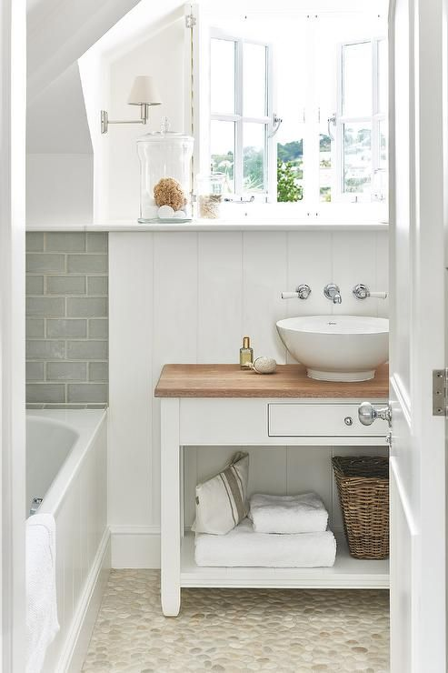 White cottage bathroom features French windows over a white washstand topped with butcher block lined with a round bowl sink under a wall-mount vintage faucet lining a vertical shiplap wall placed atop a tan pebble floor.