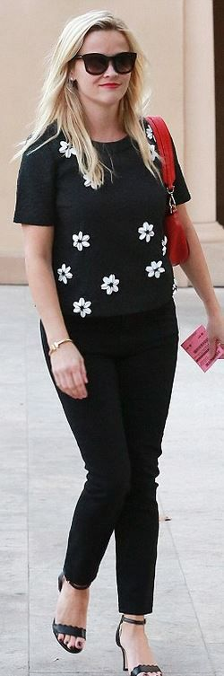 Reese Witherspoon's black wavy sandals, gold jewelry, red handbag, and floral short sleeve top