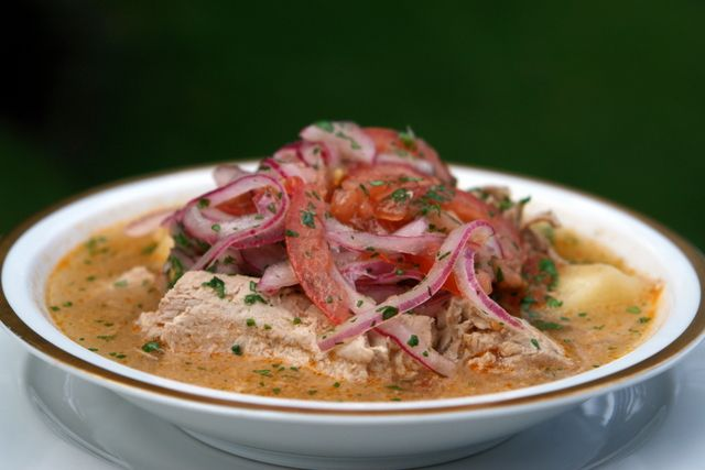Ecuadorian fish soup recipe made with fresh tuna, yuca, tomato, onions, cilantro, cumin, hot pepper and topped with pickled onions and tomatoes.