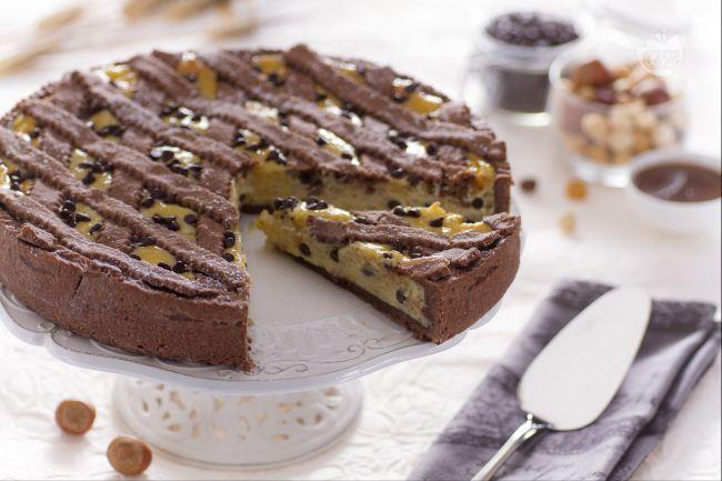 La pastiera alle nocciole e cacao è una versione originale della classica pastiera napoletana con una frolla al cacao e nocciole e ripieno di ricotta.