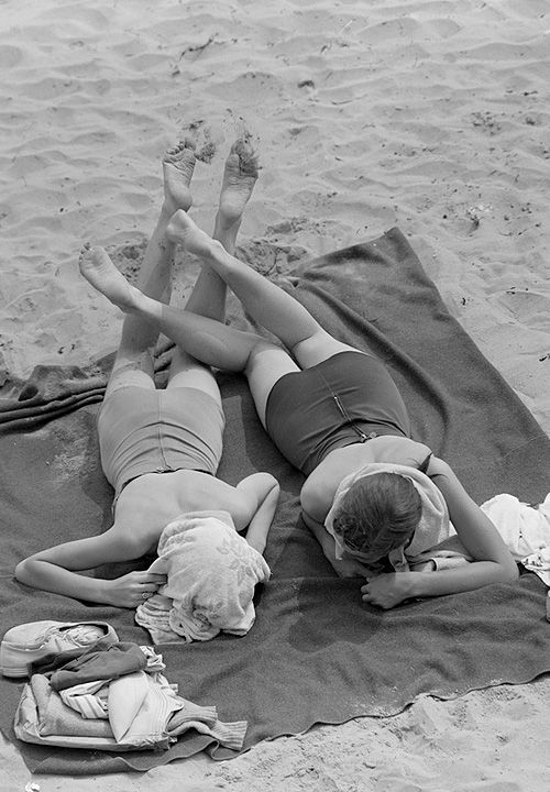 Two girls sunbathing at the beach from bpl archives