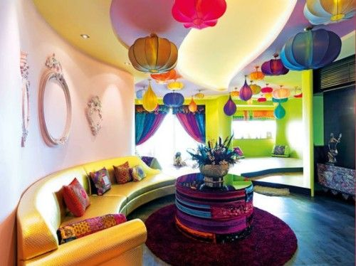 Color overload can create a lively room that is energized by bold colors that harmonize and contrast. Citrus hues on the walls are contrasted by a riot of colorful lanterns in this Moroccan influenced living room.