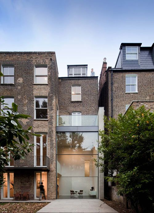 Bassett Road House by Paul+O Architects in Kensington, London. The Victorian townhouse was renovated and extended to the rear, with a double height extension featuring a motorized window.