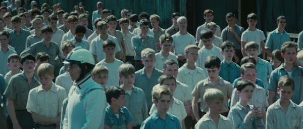 Niños del Distrito 12 de la nación de Panem, con ropa en tonos azules y grises pálidos. El equipo de vestuario arrugó alrededor de 400 trajes para tener apariencia descuidada en el día de la cosecha