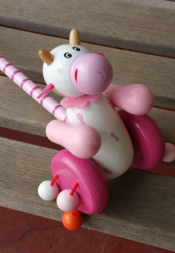 Wooden Pink Cow Push Along This traditional-style wooden toy features a cute cow and has colourful beads attached to its wheels which make a satisfying clacking noise as the little cow is pushed along.  Even toddlers who haven't quite mastered the art of walking yet enjoy watching others push and pull the mouse along.  The wooden handle has a painted ball at the end to give little hands something to grasp. Size: 50cm long Ages: 12 mths+