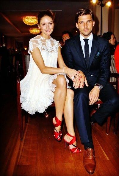 Olivia Palermo de vestido branco curto e solto, com transparência e aplicação de renda no colo. Os sapatos fogem do tradicional branco e ganham cor com a escolha do vermelho. O noivo usa azul marinho com sapatos de couro na cor marrom.