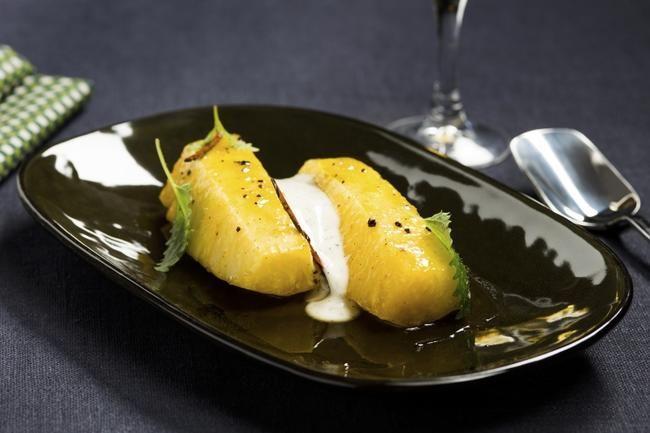 Krydderbakt ananas med vaniljekesam Ananas blir både saftigere og søtere når den bakes i ovn. En krydderlake med rom, vaniljestang, stjernea...