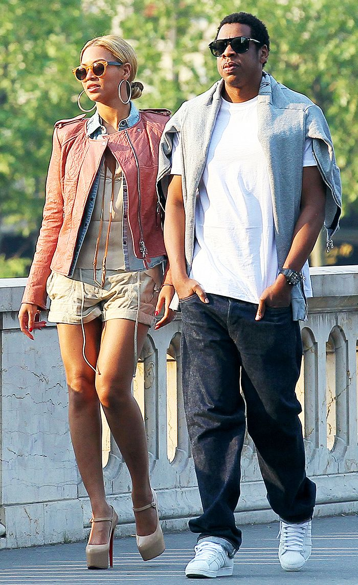 Beyoncé wears a neutral top, shorts, denim shirt, muted red leather jacket, platform Mary Jane heels, hoops, and round sunglasses