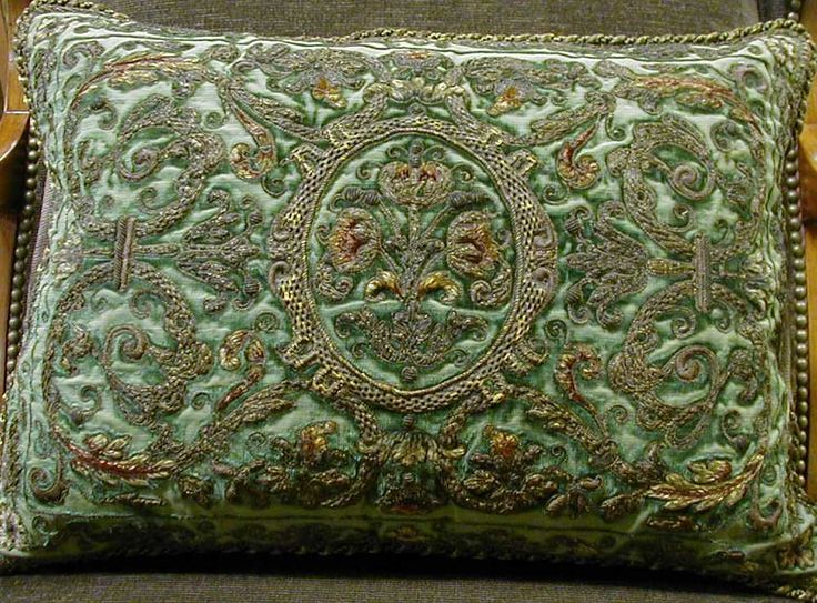 19th century French raised metal and silk embroidery work on it's original green silk velvet. A centered cartouche with flowers surrounded by a symmetrical thick floral design.